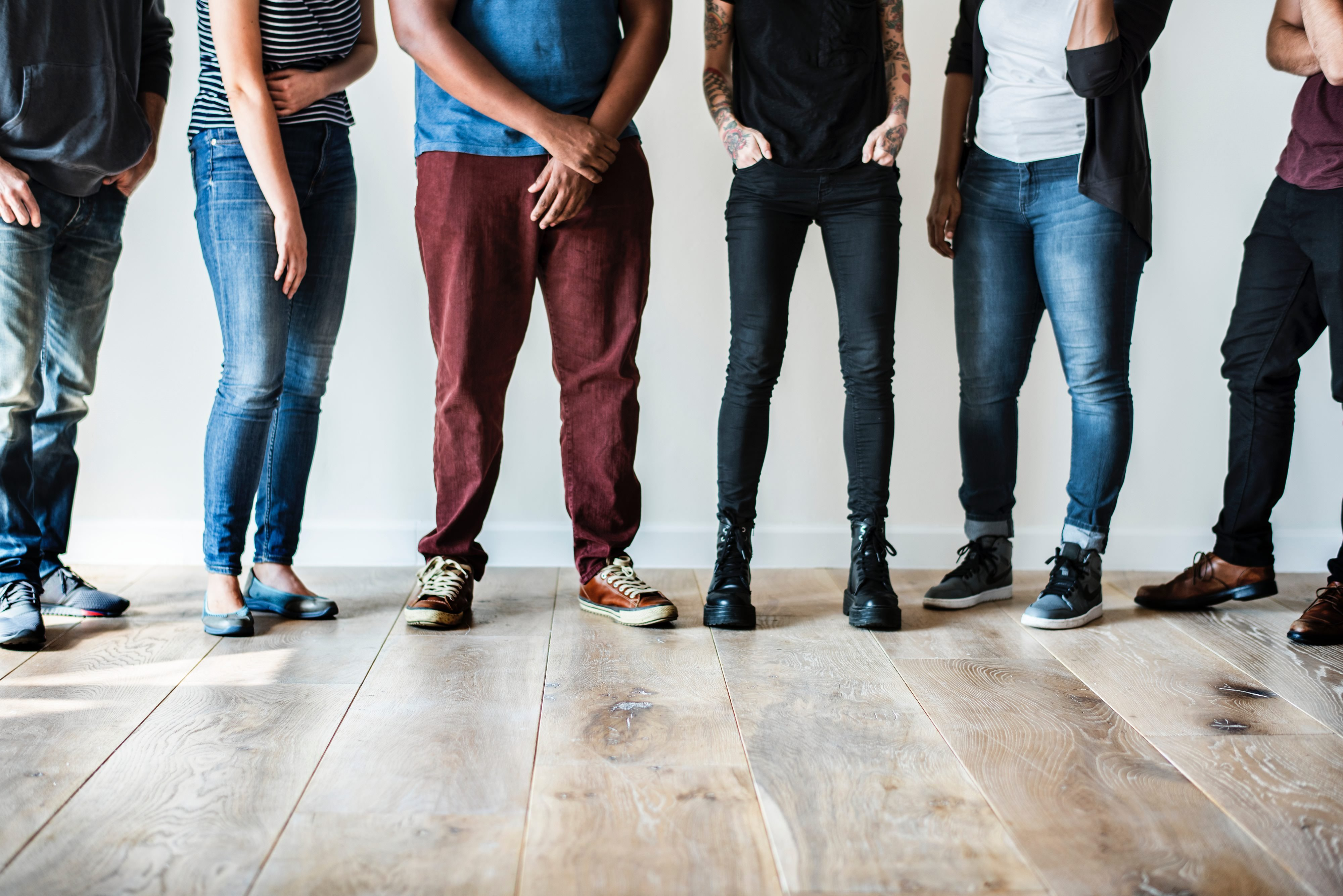 group of people standing on a hardwood floor